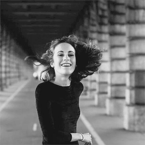 Portrait noir et blanc d'Eugénie Drion, en mouvement, sous une passerelle de métro à Paris. La photo apparaît sur le site de son association Indépendanse.