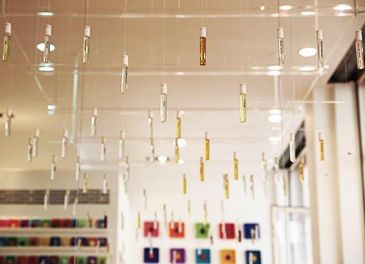 Une photo détail des ateliers parfums Sillages Paris. Un aperçu de l'orgue à parfum suspendu, contenant 64 fioles d'ingrédients purs qui composent les parfums de la marque. Dans le fond, des cadres de couleurs mettent en avant les flacons iconiques de Sillages Paris.