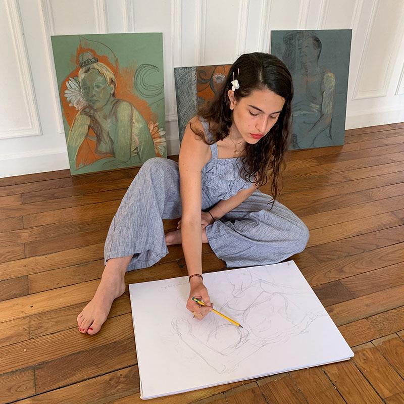 Zisla Tortello dessine par terre chez elle, certains des tableaux qu'elle a fait sont affichés derrière elle.