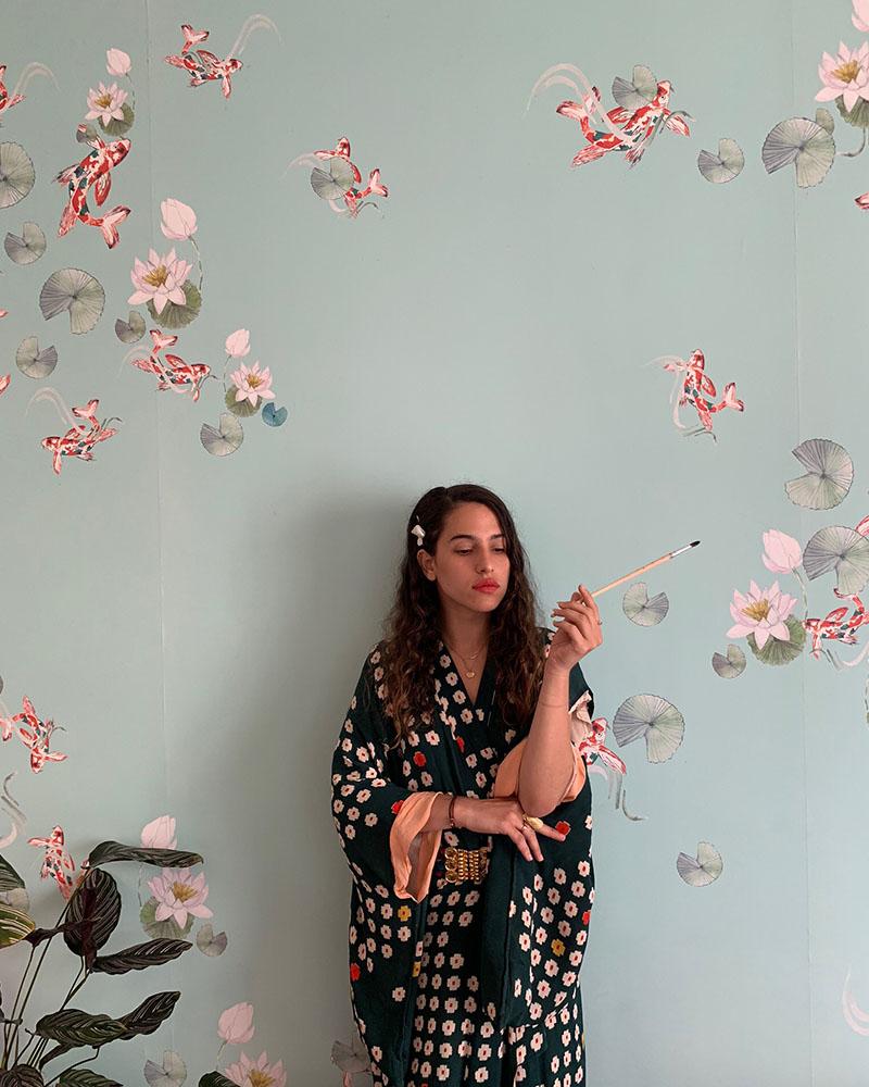 Zisla Tortello en kimono, tenant un pinceau à la main et posant devant un mur recouvert d'un papier peint qu'elle a créé